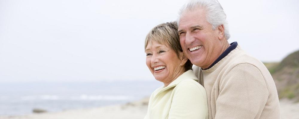 Ein Paar steht lächelnd am Strand