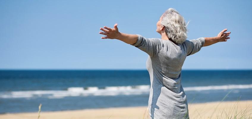 Frau steht am Strand und breitet die Hände aus